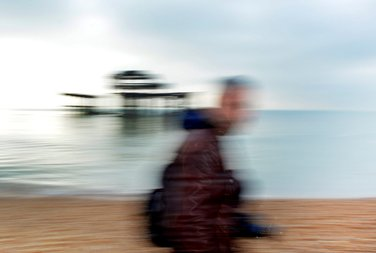 A motion blurred photo with Brighton West Pier in the background and a male student with his camera walking past in the frontground. Photo by Eva Kalpadaki.