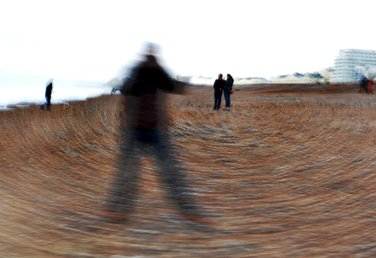 Circular motion blur photograph by Eva Kalpadaki showing a male student standing in a pose A on the pebbles in Brighton seafront with three other people in the back ground.