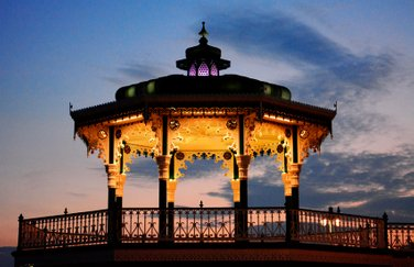 Side view of yellow lit Brighton Bandstand in the night in blue background sky. Photo by Eva Kalpadaki.